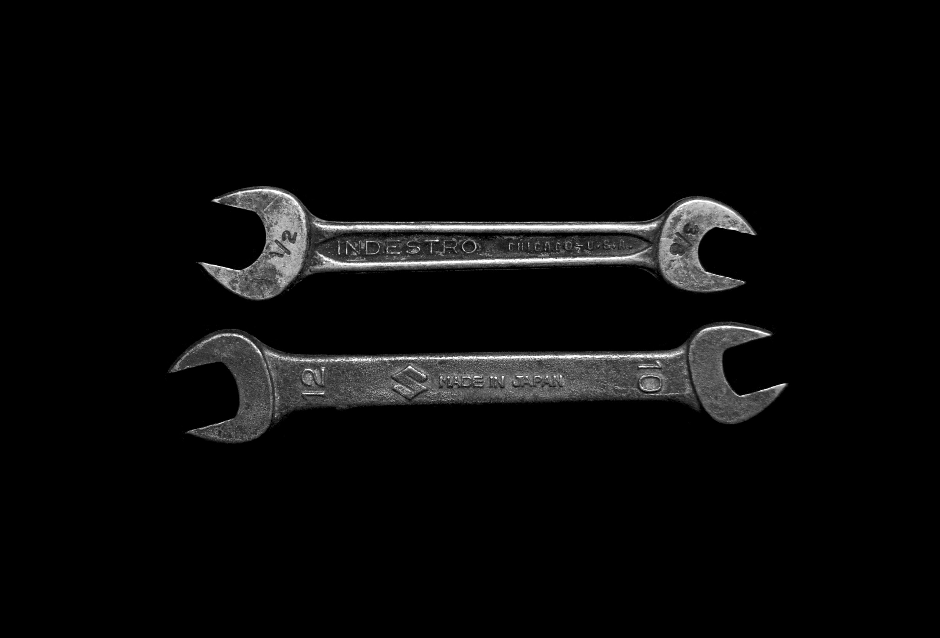 two old-fashioned box wrenches against a dark background