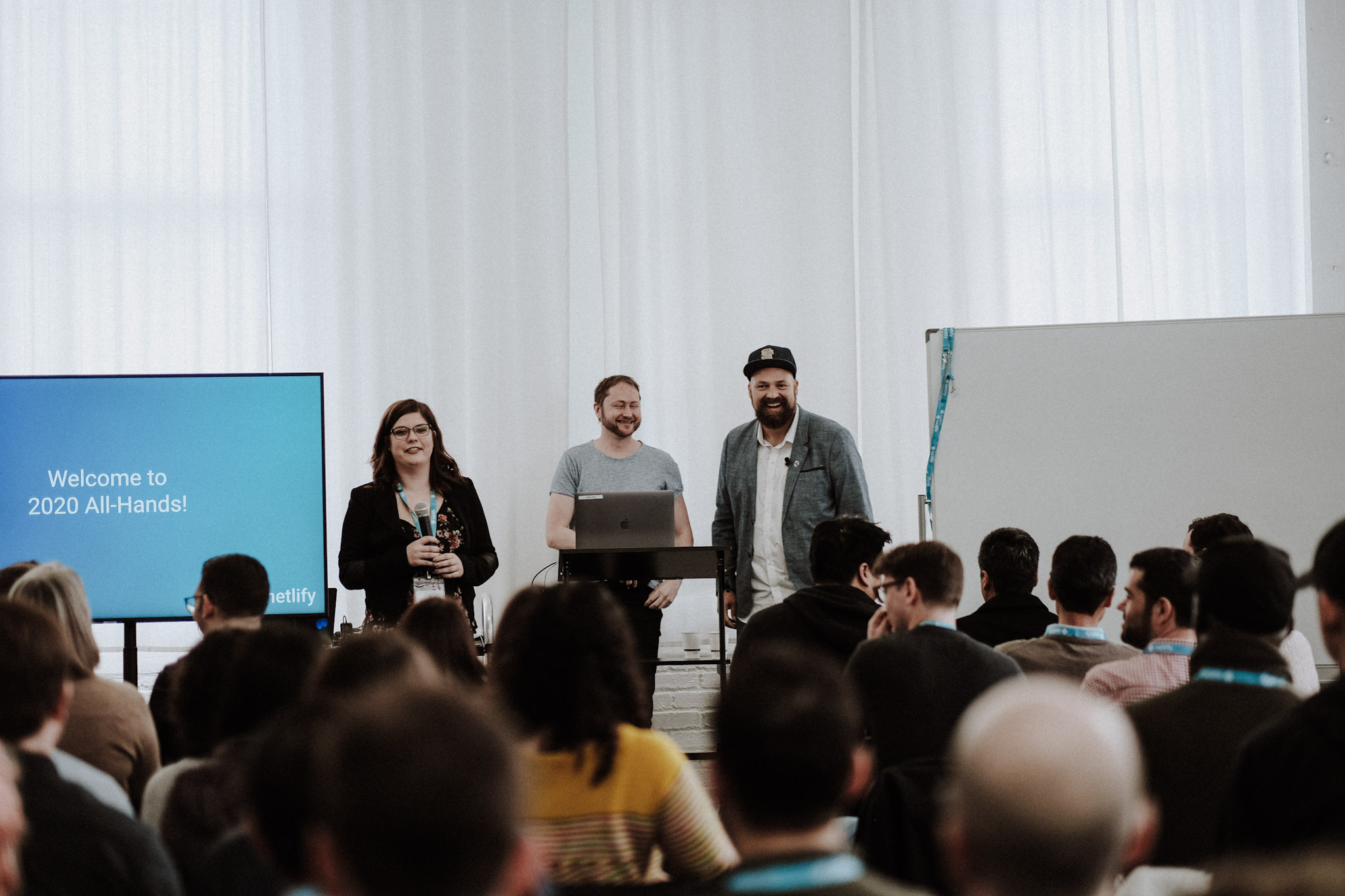 group of people seen sitting facing a stage. on stage are chris and mathias, netlify founders, and madeleine, our office manager.