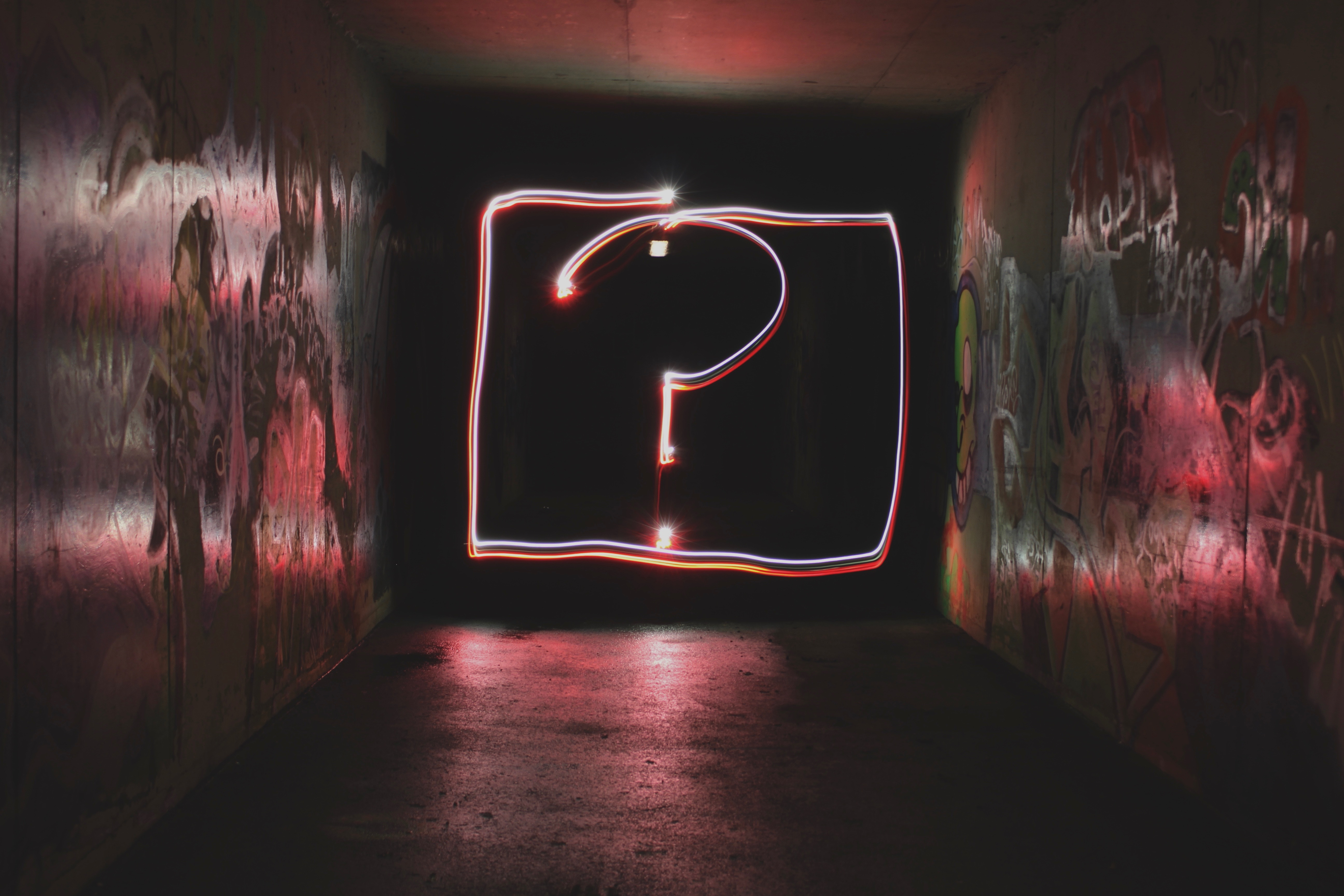 Large bright question mark at the end of a dark hallway